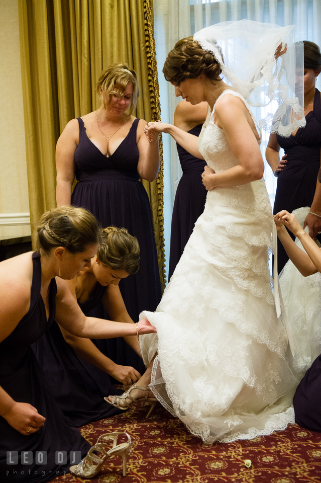 Bride getting a helping hand from Maid of Honor with her shoes. Historic Inns of Annapolis Maryland, Governor Calvert House Greek wedding, by wedding photographers of Leo Dj Photography. http://leodjphoto.com