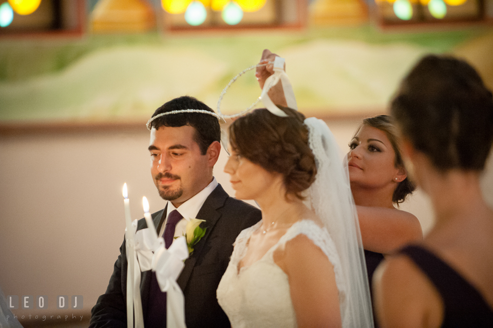 Koumbara interchanges the crowns three times during crowning ceremony. Saints Constantine and Helen Greek Orthodox Church wedding, by wedding photographers of Leo Dj Photography. http://leodjphoto.com
