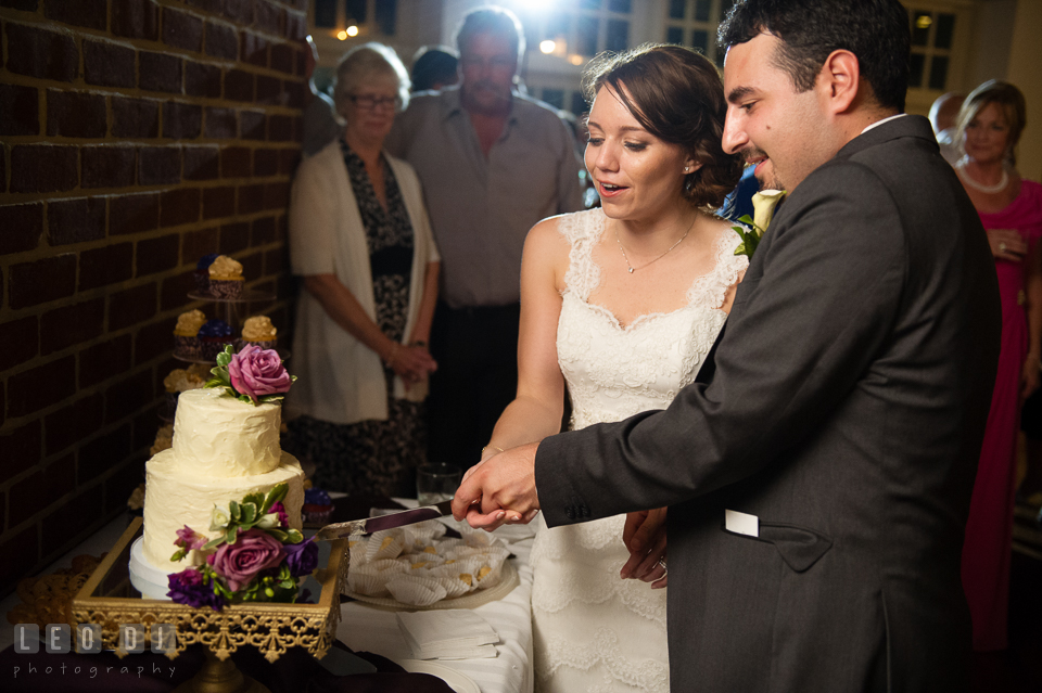 Bride and Groom during cake cutting. Cake by Sweet Hearts Patisserie. Historic Inns of Annapolis Maryland, Governor Calvert House Greek wedding, by wedding photographers of Leo Dj Photography. http://leodjphoto.com