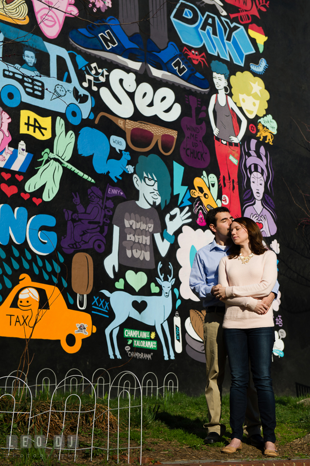 Engaged couple hugged and kissed in front of a wall mural. Washington DC pre-wedding engagement photo session at Adams Morgan and the Smithsonians, by wedding photographers of Leo Dj Photography. http://leodjphoto.com