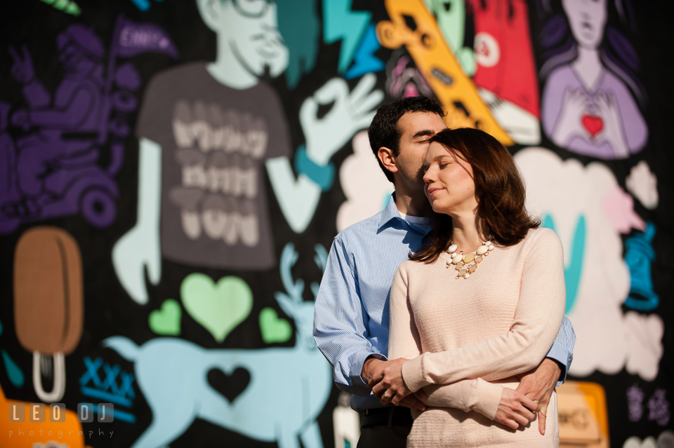 Engaged guy hugging his fiancé in front of a colorful wall mural. Washington DC pre-wedding engagement photo session at Adams Morgan and the Smithsonians, by wedding photographers of Leo Dj Photography. http://leodjphoto.com