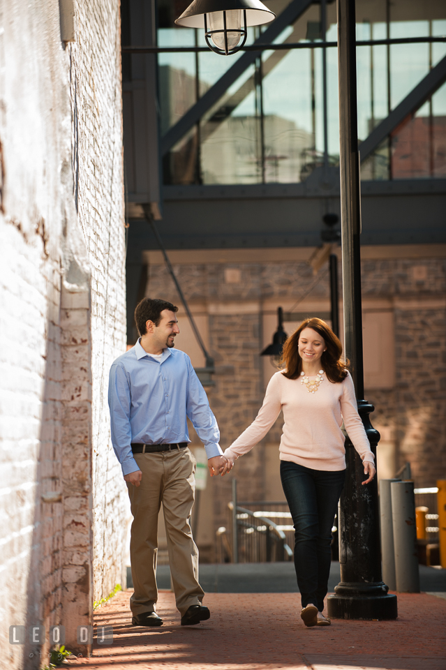 Engaged couple holding hands, walking together on a sidewalk, and smiling. Washington DC pre-wedding engagement photo session at Adams Morgan and the Smithsonians, by wedding photographers of Leo Dj Photography. http://leodjphoto.com