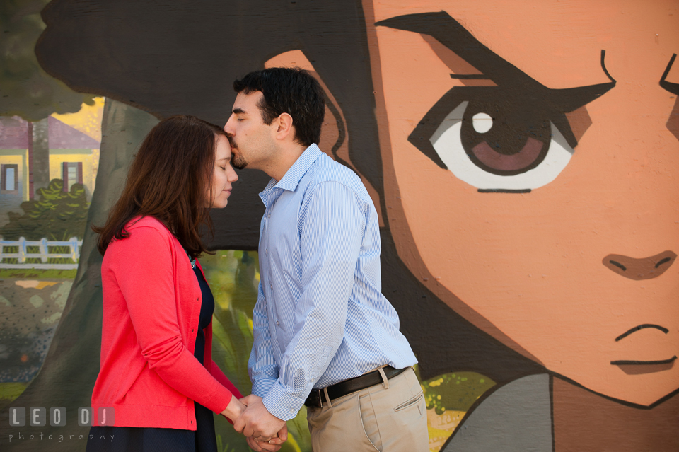Engaged couple kissing in front of a cartoon character art painting mural. Washington DC pre-wedding engagement photo session at Adams Morgan and the Smithsonians, by wedding photographers of Leo Dj Photography. http://leodjphoto.com