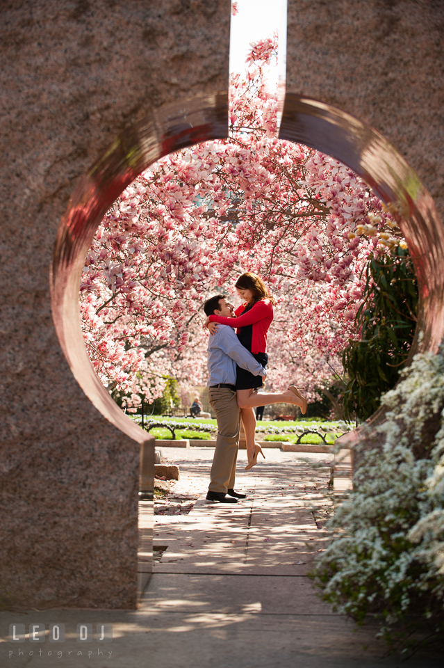 Engaged guy lifted up her fiancée up by a stone structure and magonolia trees. Washington DC pre-wedding engagement photo session at Adams Morgan and the Smithsonians, by wedding photographers of Leo Dj Photography. http://leodjphoto.com