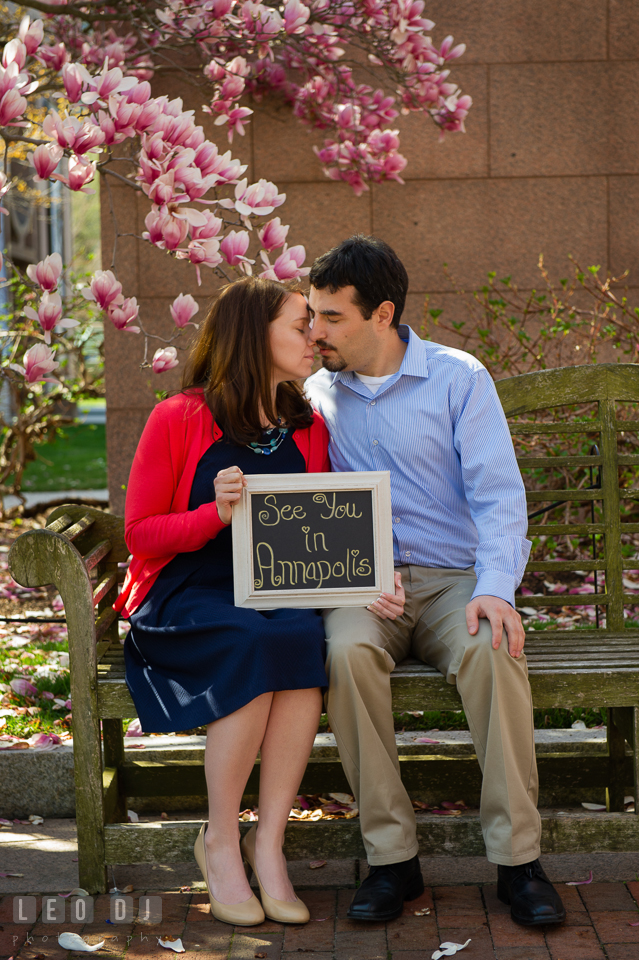 Engaged couple sitting on a bench under a magnolia tree holding a sign, See you in Annapolis for their weddingfiancé . Washington DC pre-wedding engagement photo session at Adams Morgan and the Smithsonians, by wedding photographers of Leo Dj Photography. http://leodjphoto.com
