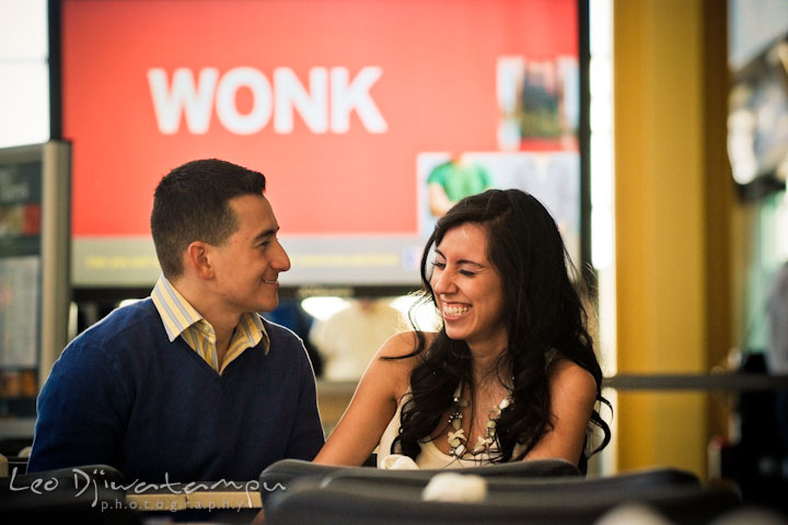 Engaged couple sitting by a restaurant table, laughing. Pre wedding engagement photo Washington DC Smithsonians museum and Ronald Reagan Washington National Airport DCA, by wedding photographer Leo Dj Photography
