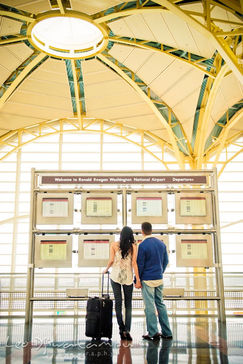 Engaged fiancé and fiancée looking at departure schedule screens. Pre wedding engagement photo Washington DC Smithsonians museum and Ronald Reagan Washington National Airport DCA, by wedding photographer Leo Dj Photography
