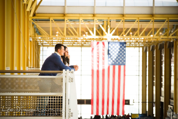 Engaged guy holding fiancée's hand on balcony. American flag in the background. Pre wedding engagement photo Washington DC Smithsonians museum and Ronald Reagan Washington National Airport DCA, by wedding photographer Leo Dj Photography