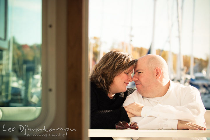 Engaged couple cuddling on a boat. Annapolis Downtown USNA Pre-wedding Engagement Photographer, Leo Dj Photography