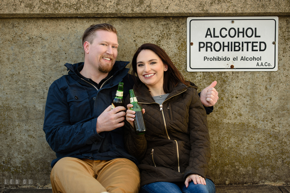 Jonas Green Park Annapolis Maryland engaged man and fiancee holding beer bottles by an alcohol prohibited sign photo by Leo Dj Photography.