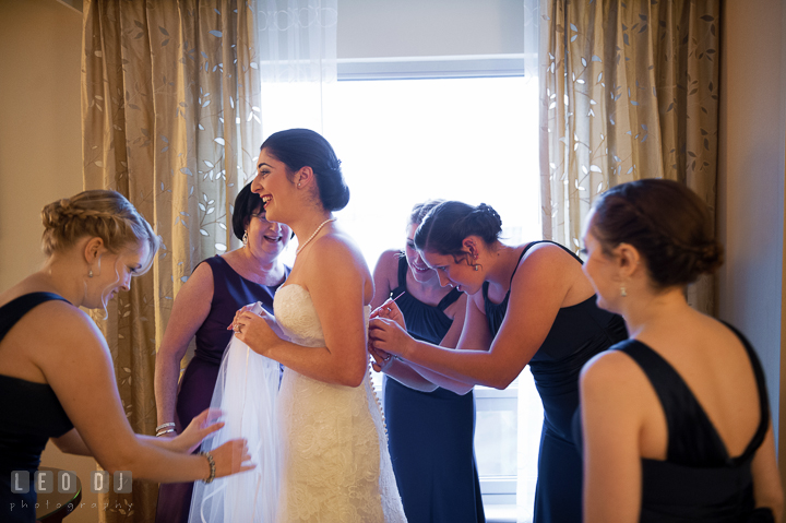 Bride putting on wedding gown with help from Mother, bridesmaids and maid of honor. Marriott Washingtonian Center wedding at Gaithersburg Maryland, by wedding photographers of Leo Dj Photography. http://leodjphoto.com