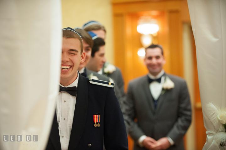 Groom under chuppah laughing listeing to Groomsman's speech. Marriott Washingtonian Center wedding at Gaithersburg Maryland, by wedding photographers of Leo Dj Photography. http://leodjphoto.com