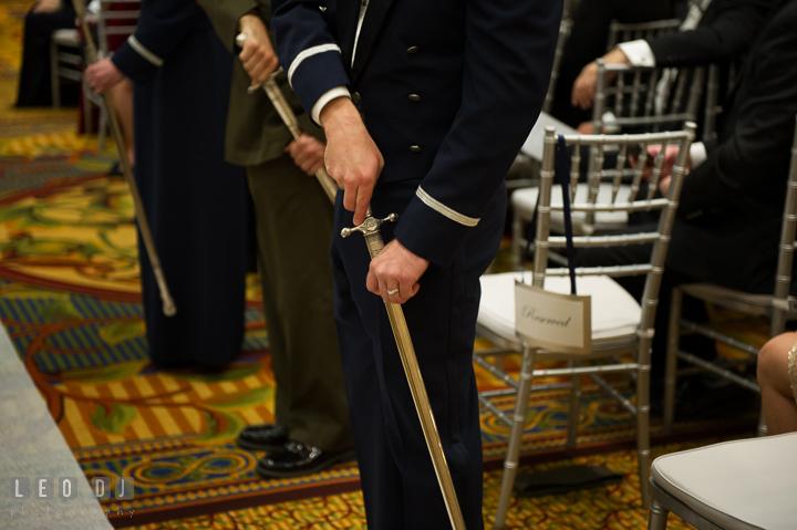 US Air Force officers sheath their swords after the military wedding cordon. Marriott Washingtonian Center wedding at Gaithersburg Maryland, by wedding photographers of Leo Dj Photography. http://leodjphoto.com