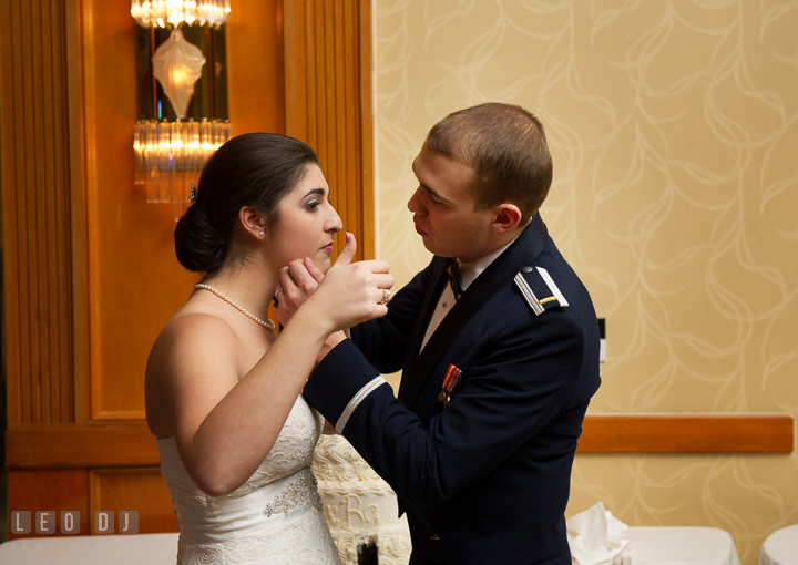 Groom wiping of cake from Bride's cheek. Marriott Washingtonian Center wedding at Gaithersburg Maryland, by wedding photographers of Leo Dj Photography. http://leodjphoto.com