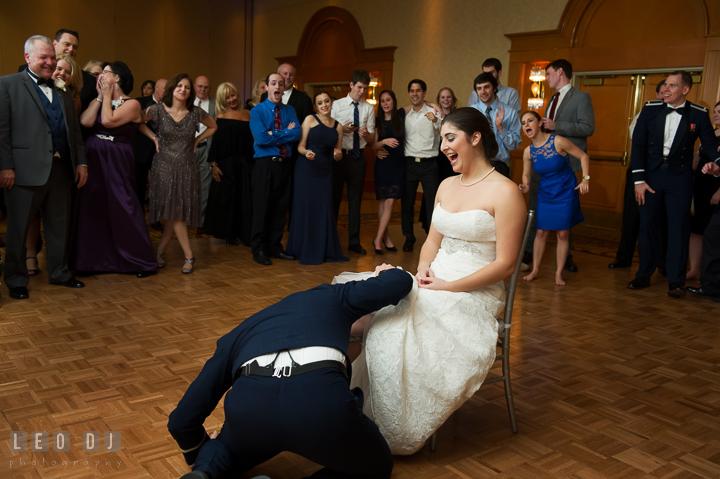 Groom trying to peek under Brides wedding dress to find garter. Marriott Washingtonian Center wedding at Gaithersburg Maryland, by wedding photographers of Leo Dj Photography. http://leodjphoto.com