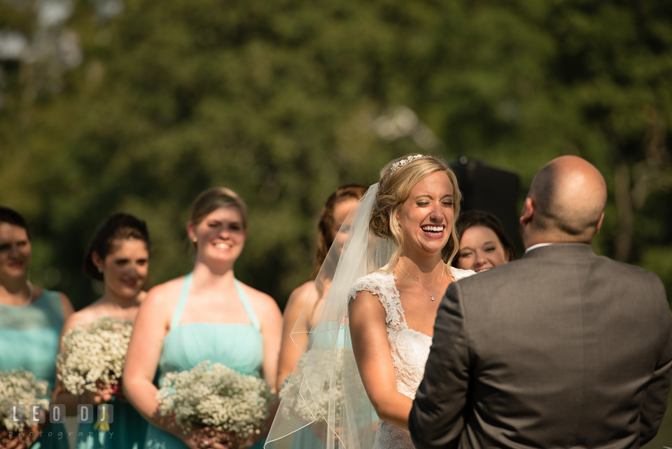 The Oaks Waterfront Inn Bride laughing while Groom reciting vows during the ceremony Flowers photo by Leo Dj Photography