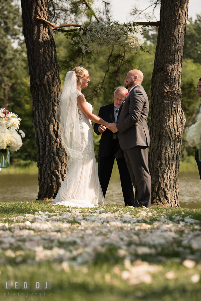 The Oaks Waterfront Inn Bride and Groom holding hands during ceremony photo by Leo Dj Photography