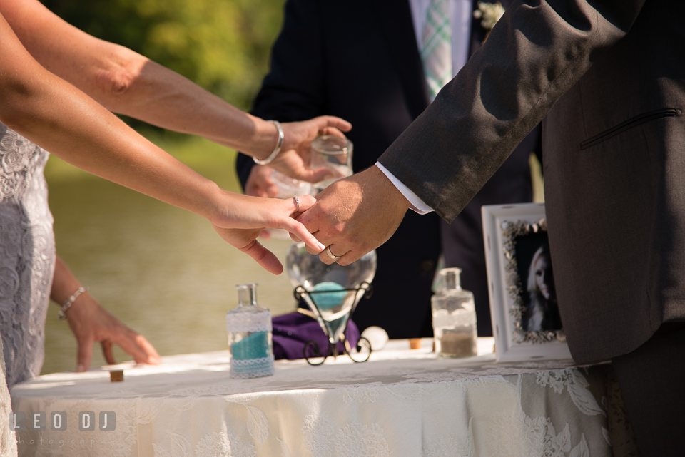 The Oaks Waterfront Inn Bride and Groom holding hands while parents pouring unity sand photo by Leo Dj Photography