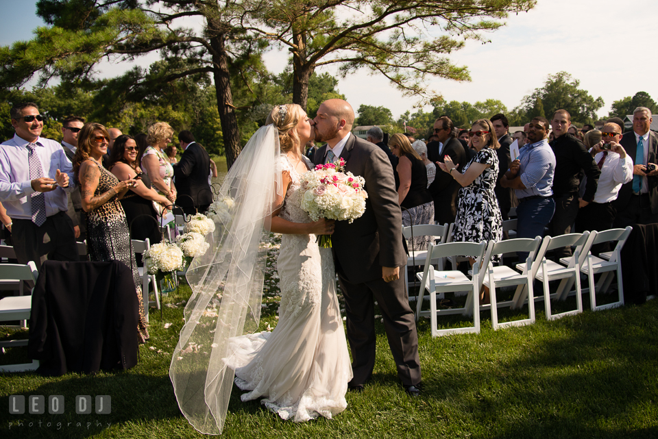 The Oaks Waterfront Inn Bride and Groom kissing as they walk out of the aisle during ceremony recessional photo by Leo Dj Photography
