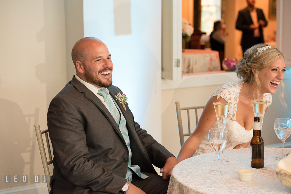 The Oaks Waterfront Inn Bride and Groom at sweetheart table laughing to Maid of Honor and Best Man's toast speeches photo by Leo Dj Photography