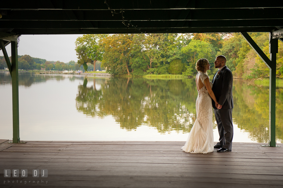 The Oaks Waterfront Inn Bride and Groom almost kiss on the dock with gorgeous water view photo by Leo Dj Photography