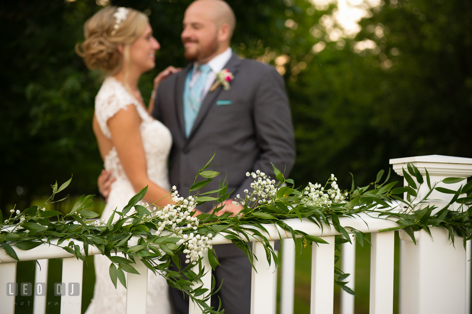 The Oaks Waterfront Inn Bride and Groom on bridge with flowers by florist Seasonal Flowers photo by Leo Dj Photography