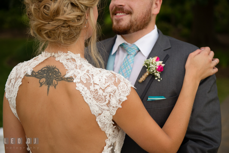 Bride with open dress back holding Groom showing her tattoo. The Oaks Waterfront Inn wedding, St Michaels, Eastern Shore, Maryland, by wedding photographers of Leo Dj Photography. http://leodjphoto.com