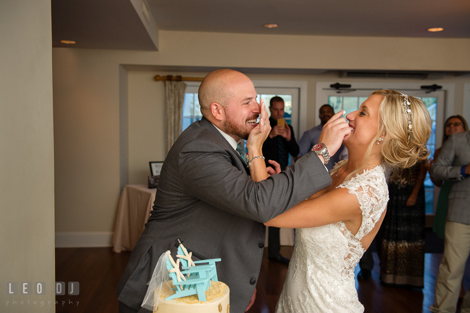 The Oaks Waterfront Inn Bride and Groom smash icing on each other during cake cutting photo by Leo Dj Photography