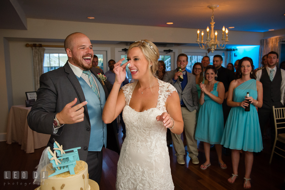 The Oaks Waterfront Inn Bride and Groom laughing after smearing cake icing on each other photo by Leo Dj Photography