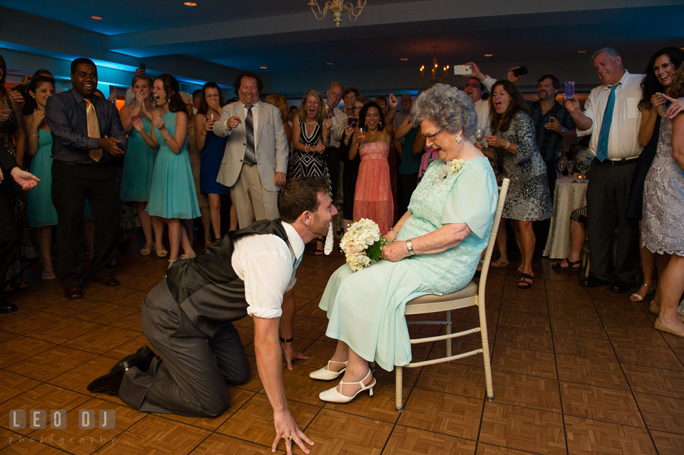 The Oaks Waterfront Inn Groomsman crawling with garter in front of grandma photo by Leo Dj Photography