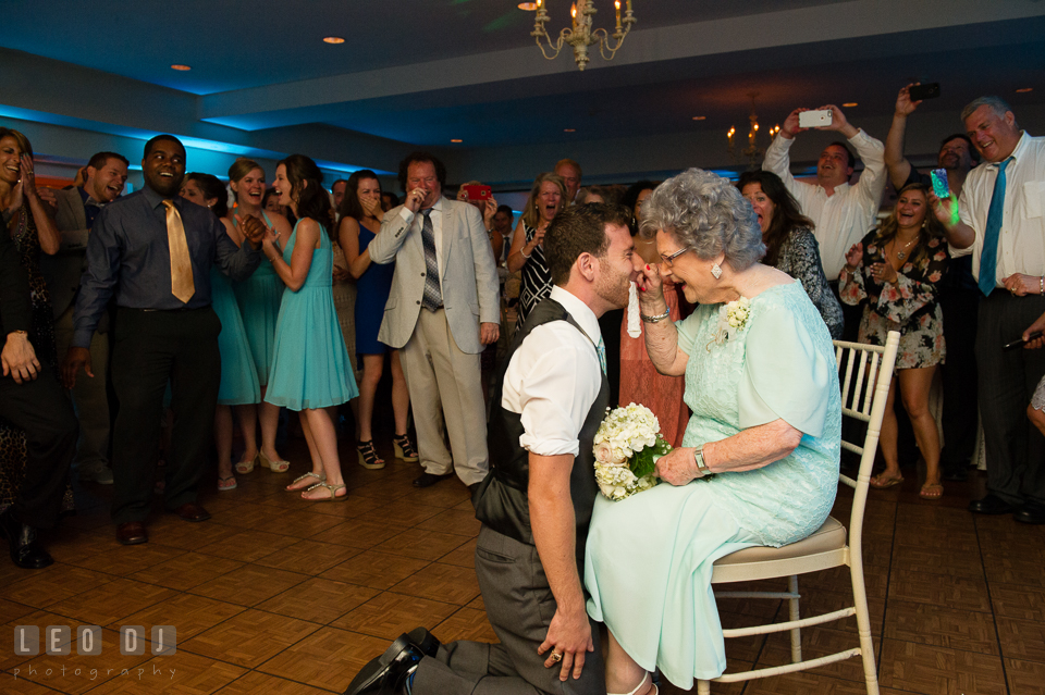 The Oaks Waterfront Inn Grandmother pinched nose of Groomsman kneeling with garter photo by Leo Dj Photography