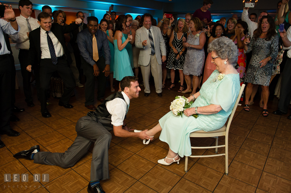 The Oaks Waterfront Inn Groomsman almost laying on floor putting garter on Grandmother's leg by Leo Dj Photography