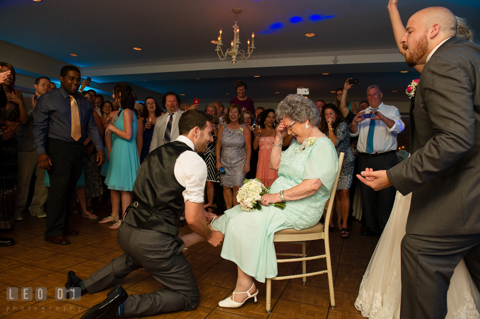The Oaks Waterfront Inn Groomsman put garter on Grandmother, cheered on by Bride, Groom and all guests photo by Leo Dj Photography