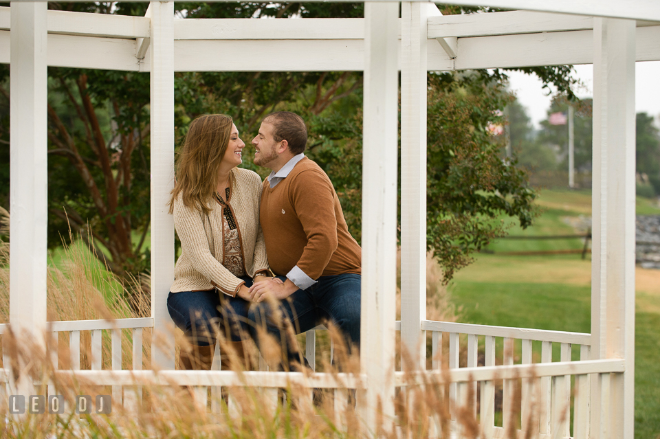 Engaged couple sitting underneath a gazebo, cuddling and laughing. Eastern Shore Maryland pre-wedding engagement photo session at St Michaels MD, by wedding photographers of Leo Dj Photography. http://leodjphoto.com