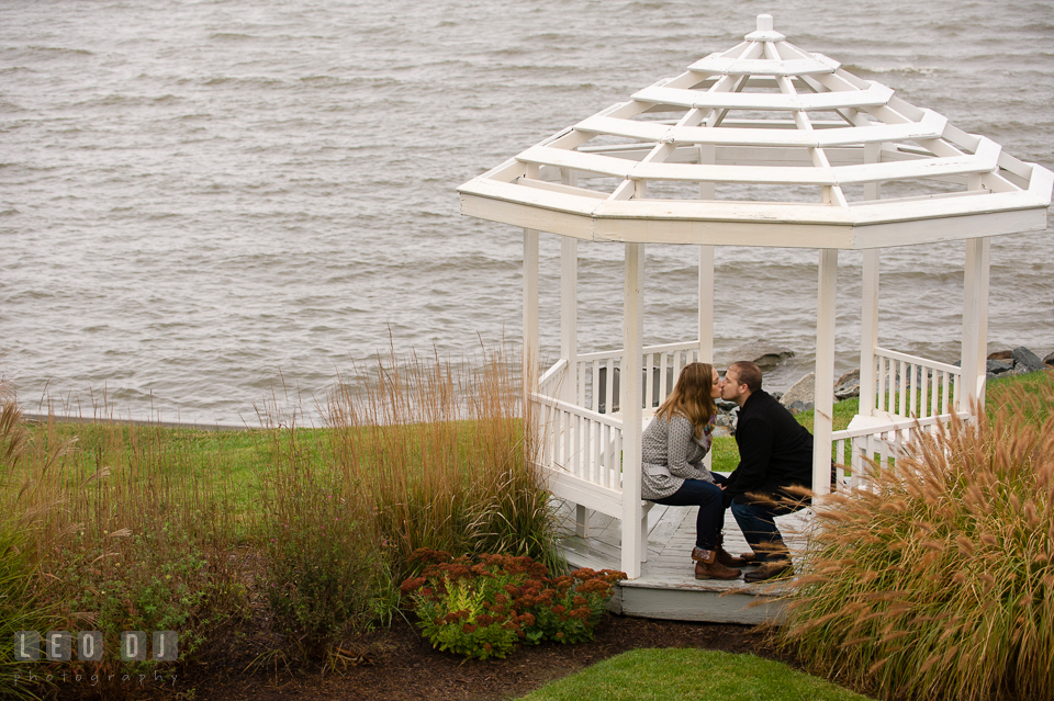 Engaged couple kissing under a gazebo by the water. Eastern Shore Maryland pre-wedding engagement photo session at St Michaels MD, by wedding photographers of Leo Dj Photography. http://leodjphoto.com