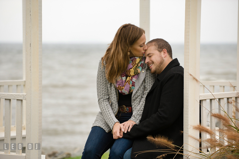Engaged girl kissing her fiancé, under the gazebo by the water. Eastern Shore Maryland pre-wedding engagement photo session at St Michaels MD, by wedding photographers of Leo Dj Photography. http://leodjphoto.com