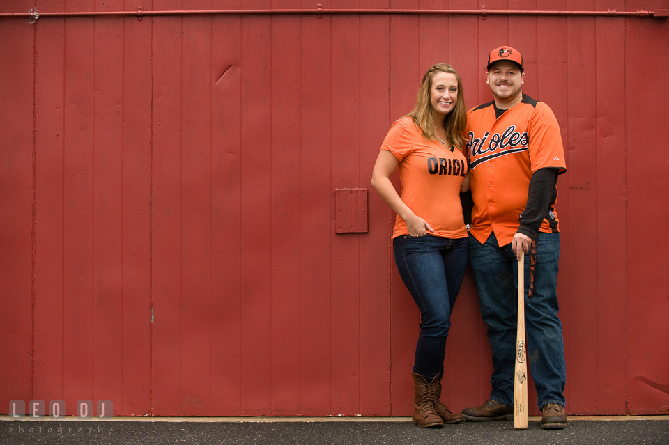 Engaged couple posing with Baltimore Orioles jersey, hat, and a Louisville Slugger baseball bat. Eastern Shore Maryland pre-wedding engagement photo session at St Michaels MD, by wedding photographers of Leo Dj Photography. http://leodjphoto.com