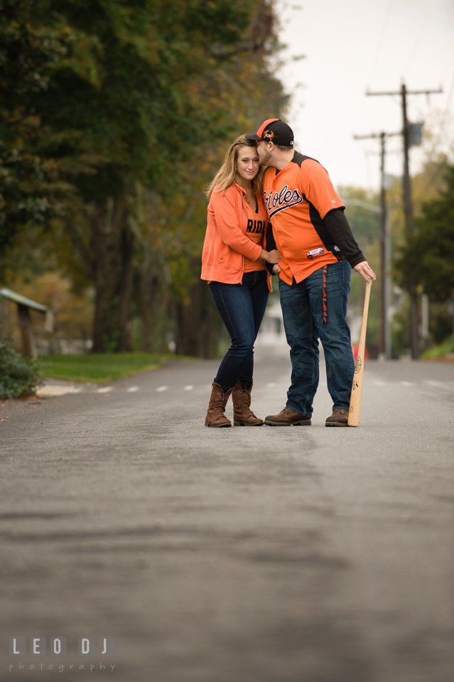 Engaged man, holding Louisville Slugger baseball bat, kissing his fiancee, both wearing Baltimore Orioles apparel. Eastern Shore Maryland pre-wedding engagement photo session at St Michaels MD, by wedding photographers of Leo Dj Photography. http://leodjphoto.com