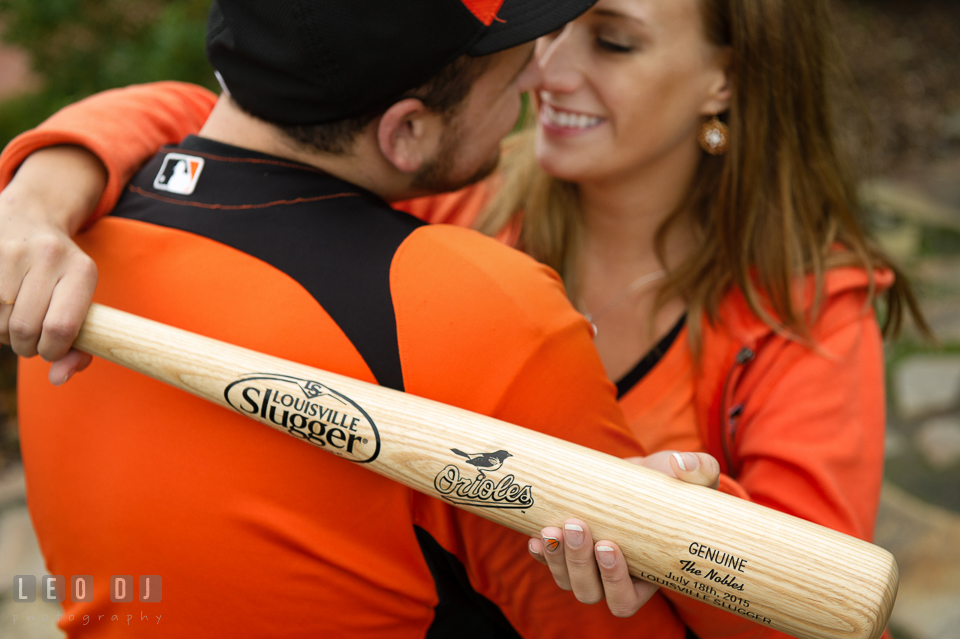 Girl embracing her fiance while holding Baltimore Orioles Louisville Slugger baseball bat. Eastern Shore Maryland pre-wedding engagement photo session at St Michaels MD, by wedding photographers of Leo Dj Photography. http://leodjphoto.com