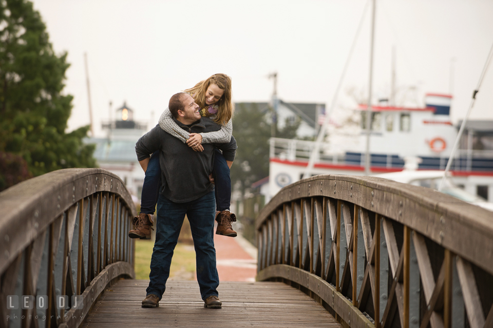 Engaged man carrying his fiancee on his back while walking on the bridge by the boat dock marina. Eastern Shore Maryland pre-wedding engagement photo session at St Michaels MD, by wedding photographers of Leo Dj Photography. http://leodjphoto.com