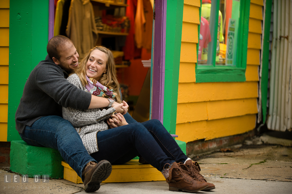 Engaged girl snuggled with her fiancé in front of a gift shop. Eastern Shore Maryland pre-wedding engagement photo session at St Michaels MD, by wedding photographers of Leo Dj Photography. http://leodjphoto.com