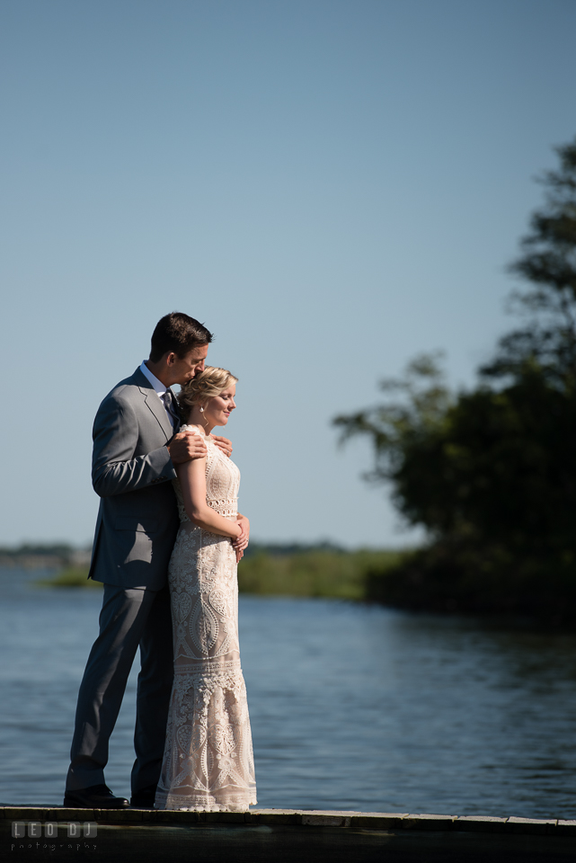 Kent Manor Inn wedding groom embracing bride by the water on the boat pier dock photo by Leo Dj Photography