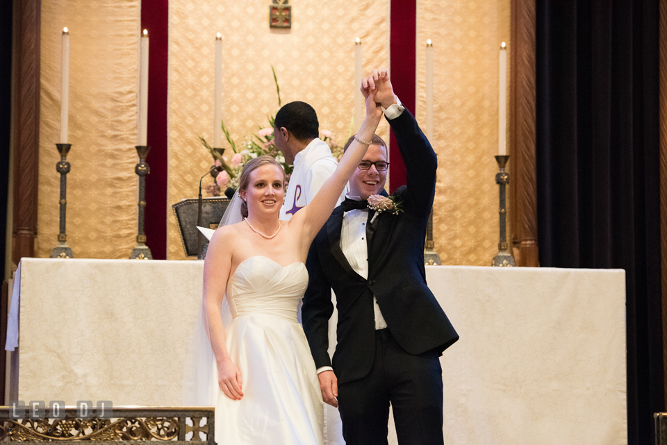 Christ Lutheran Church Inner Harbor Baltimore Maryland Bride Groom lift up hands showing rings photo by Leo Dj Photography