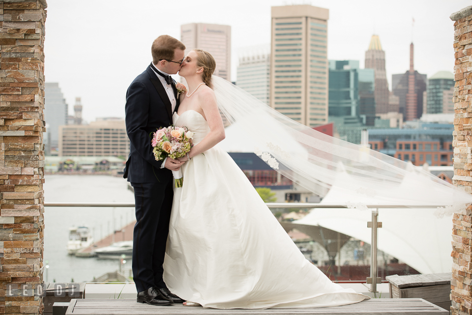 Charm City Wedding Bride and Groom kissing with Baltimore downtown Inner Harbor view photo by Leo Dj Photography