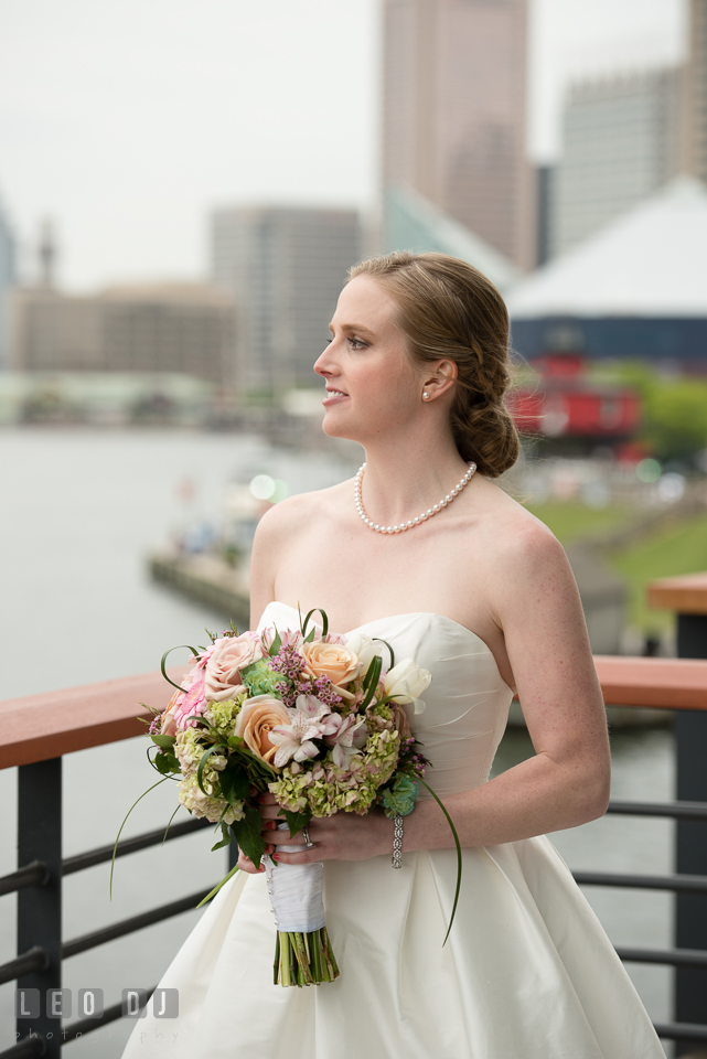 Charm City Baltimore Bride with flower bouquet from Petal Pusher Florist and wedding gown from Francesca's Bridal on Four Seasons Hotel balcony photo by Leo Dj Photography
