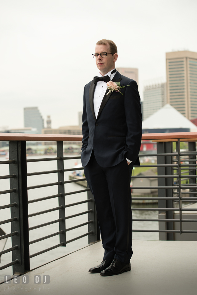 Charm City Baltimore wedding Groom posing in Four Seasons Hotel balcony photo by Leo Dj Photography