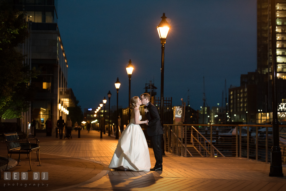 Four Seasons Hotel Baltimore wedding Bride and Groom kissing on the boardwalk with street lights photo by Leo Dj Photography