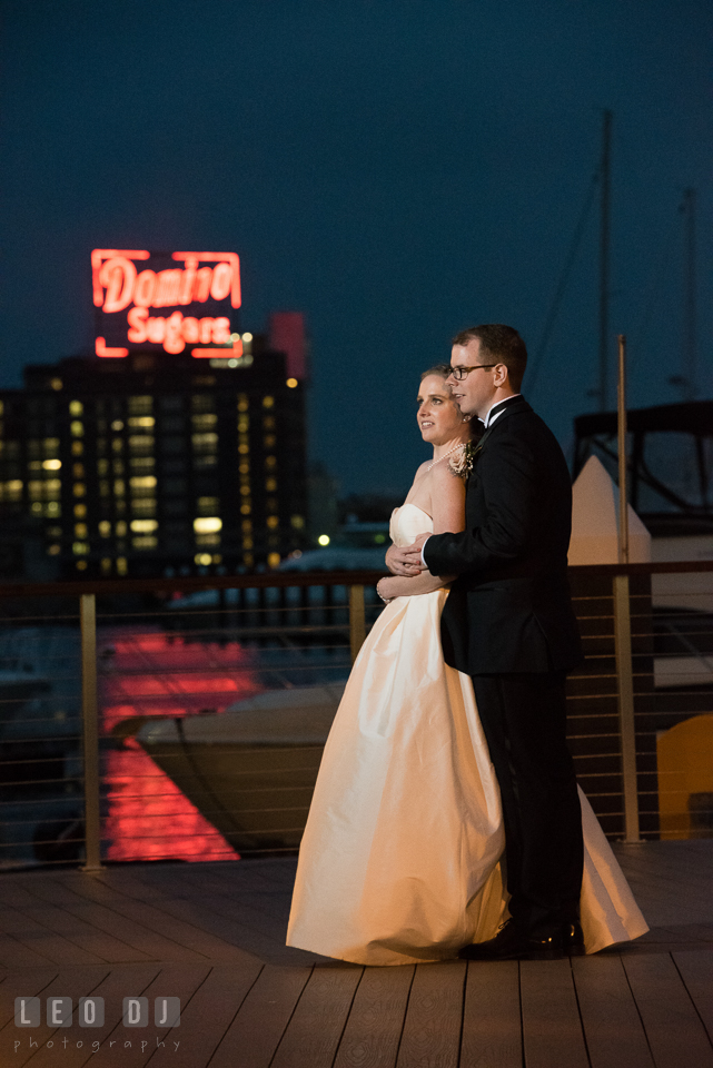 Charm City Baltimore wedding Bride and Groom hugging with Domino Sugar Plant background photo by Leo Dj Photography