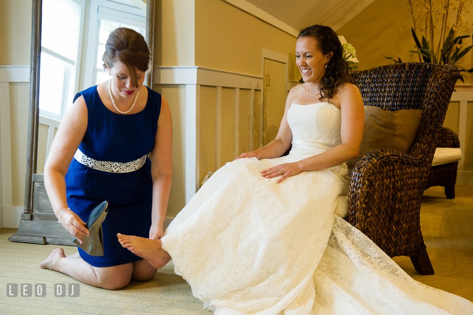 Maid of Honor help Bride put on her shoes. Kent Island Maryland Chesapeake Bay Beach Club wedding photo, by wedding photographers of Leo Dj Photography. http://leodjphoto.com