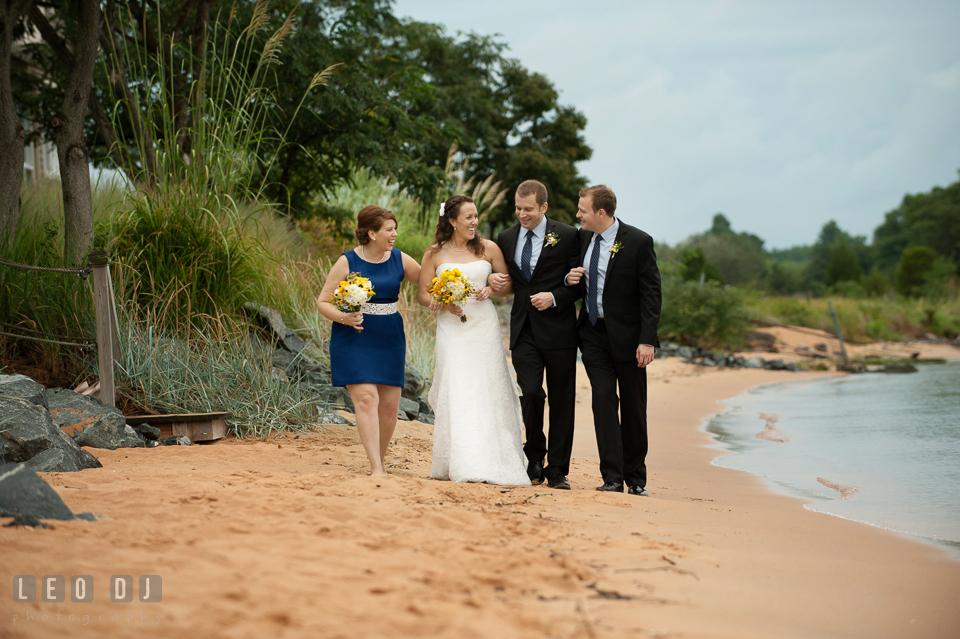 Bride, Groom, Maid of Honor, and Best Man walking together on the beach. Kent Island Maryland Chesapeake Bay Beach Club wedding photo, by wedding photographers of Leo Dj Photography. http://leodjphoto.com